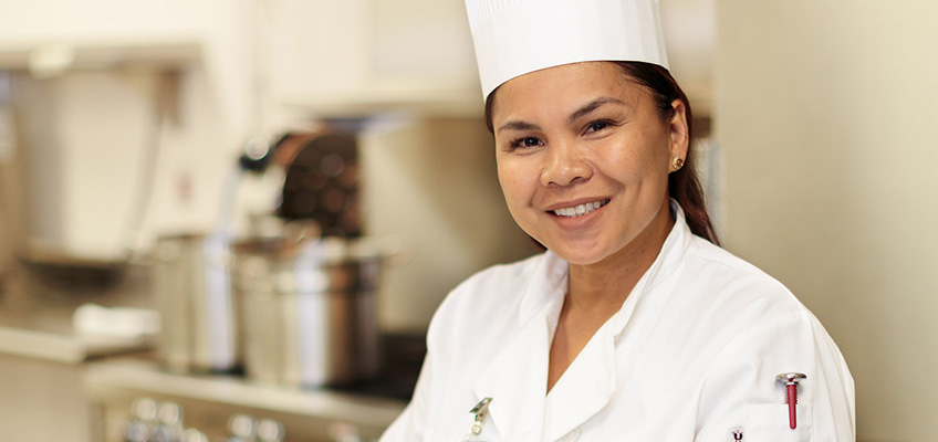 A staff member in the kitchen smiling.