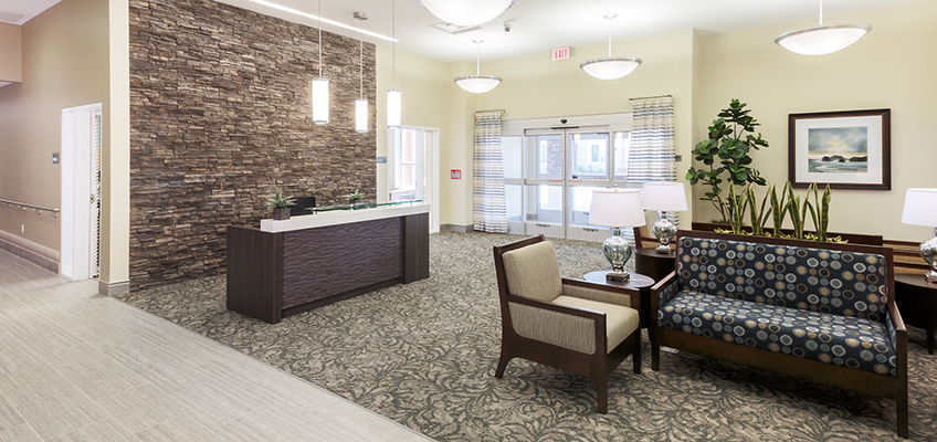 A receptionist desk with a stone wall behind it and resident lounge space.