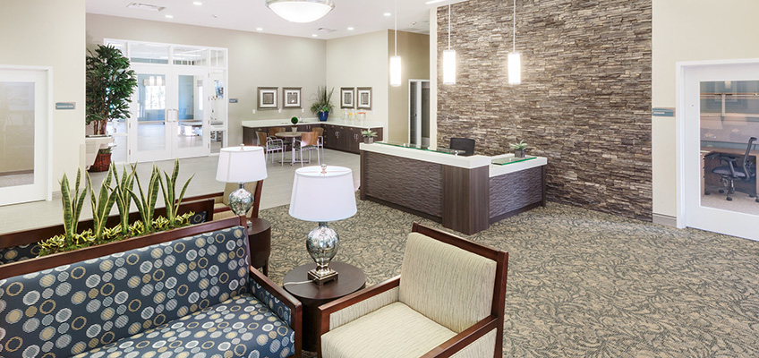 A reception desk with a stone wall behind it, and a resident lounge space in front of it.