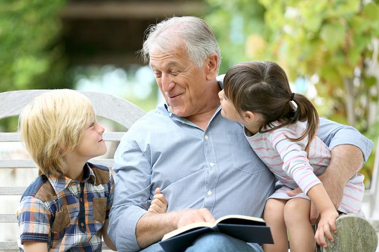 elderly man reading to his grandchildren