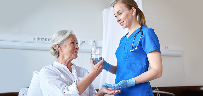 nurse tending to a patient and giving her medicine