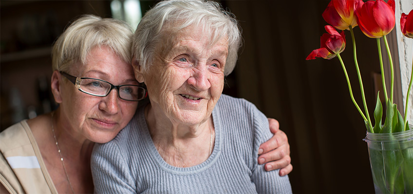 woman looking pensively with her arm around a patient