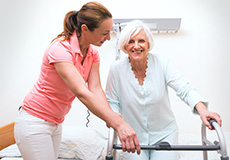 nurse helping woman with a walker