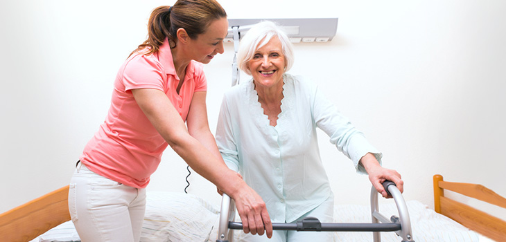 A caregiver helping a senior walk with her walker.
