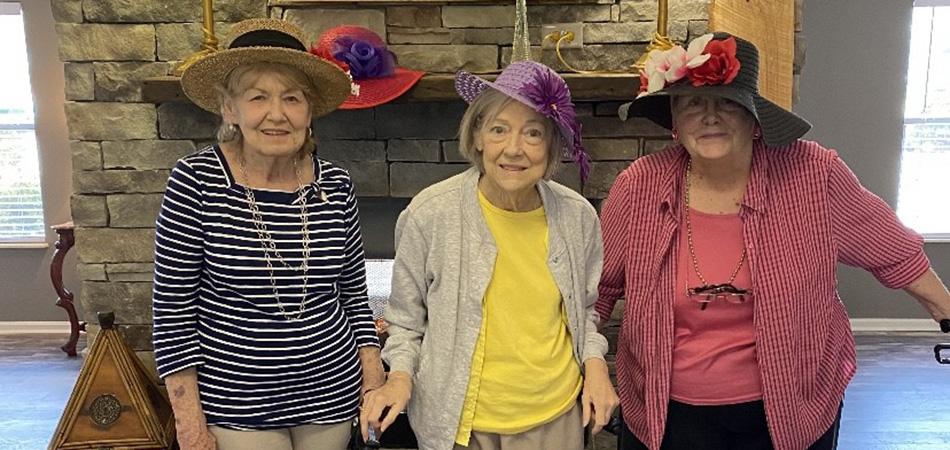 Three lovely ladies wearing fabulous hats