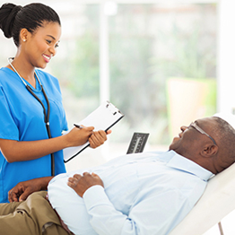 smiling nurse holding clipboard speaking with male patient that is lying down
