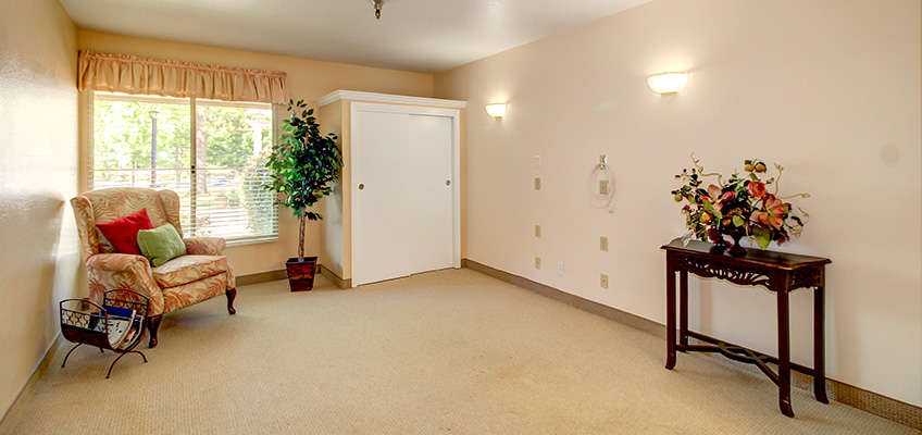 resident room with wing back chair & plants ready for occupancy