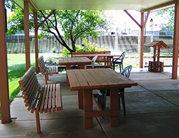 outdoor seating area with benches and green trees surrounding it