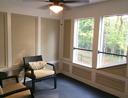 room with a ceiling fan and a sitting chair looking out the windows to green trees