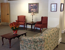 Benson manor waiting room with a couch and chairs