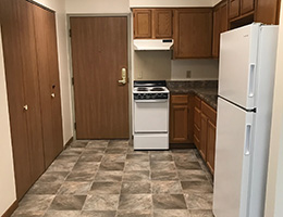 small kitchen with tiled floor, dark wood cabinets, stove and fridge