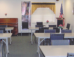 Cocalico conference area with podium, chairs and a piano
