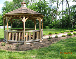 outdoor gazebo area with a nicely shrubbed walkway