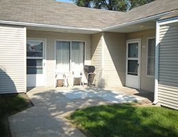 Great Plains community housing entrance with front door, windows a walkway and grass