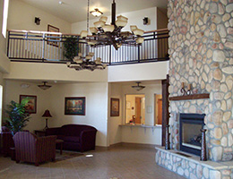Harvest Pointe's lobby with stone fireplace, seating area and upstairs hallway