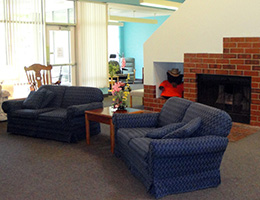 lobby inside the facility with couches and a fireplace and large glass wall