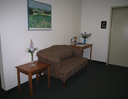 Laurel Park elevator and hallway with couch and side tables