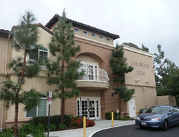 Los Arcos front of building with tall pine trees