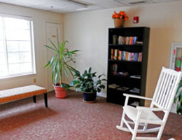 Mabel Meshack sitting area with rocking chair and bookcase full of books