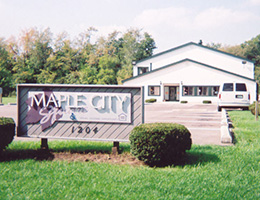 maple city square sign with the building behind it