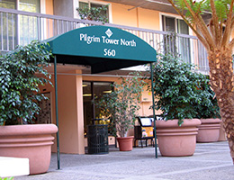 Pilgrim North entrance with awning with huge potted plants