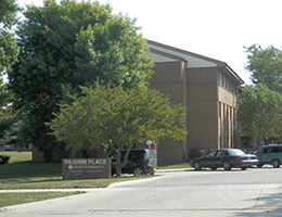 Pilgrim Place street entrance to the community with cars in the lot and trees surrounding the community building
