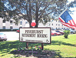 Pinehurst Retirement Housing sign with flag and balloons