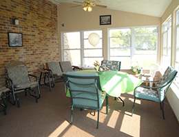 Sun room seating area with brick wall and many windows letting the light shine in