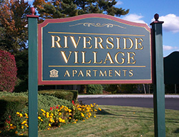 Riverside Village apartments wooden sign