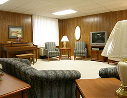 comfortable living area with a large space in the middle of the room, and a piano, couches and television on the sides