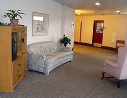 Stone Creek waiting area with couches and TV