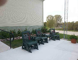 Outside sitting area with chairs and plants behind