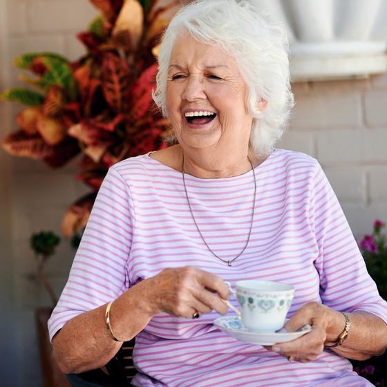 elderly woman with a cup of tea smiling