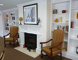 sitting area by a fireplace with shelving on either side