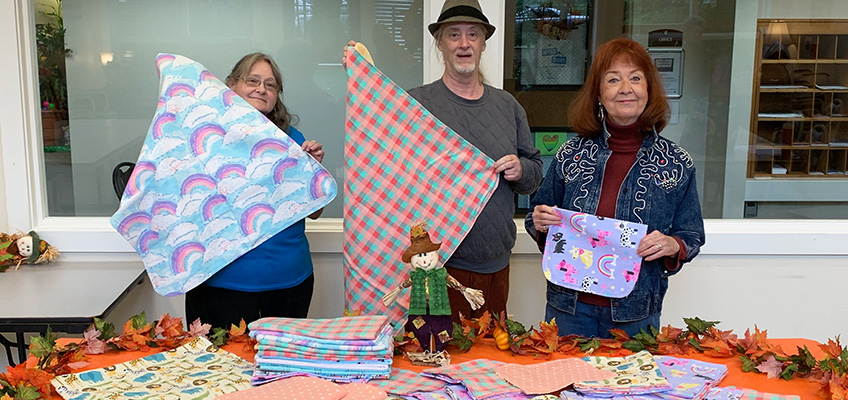 three residents showing off their sewn and quilted blankets