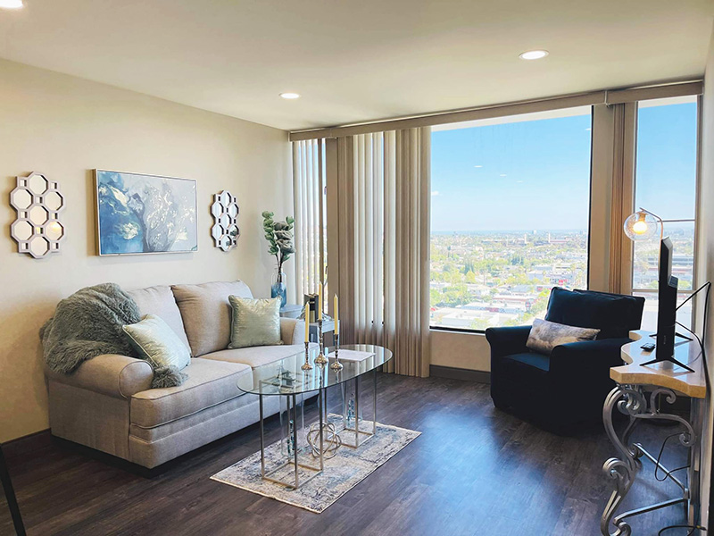 Living room with large windows at Bixby Knolls