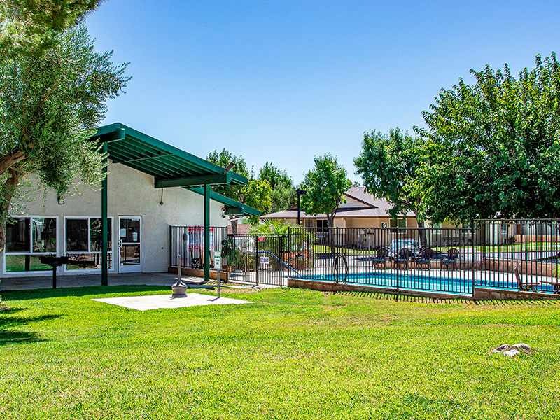 Community pool with grassy area out front and trees.