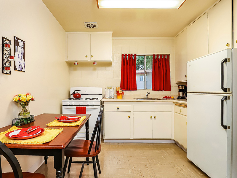Studio kitchen area with kitchenette, window above the sink, oven and refrigerator.