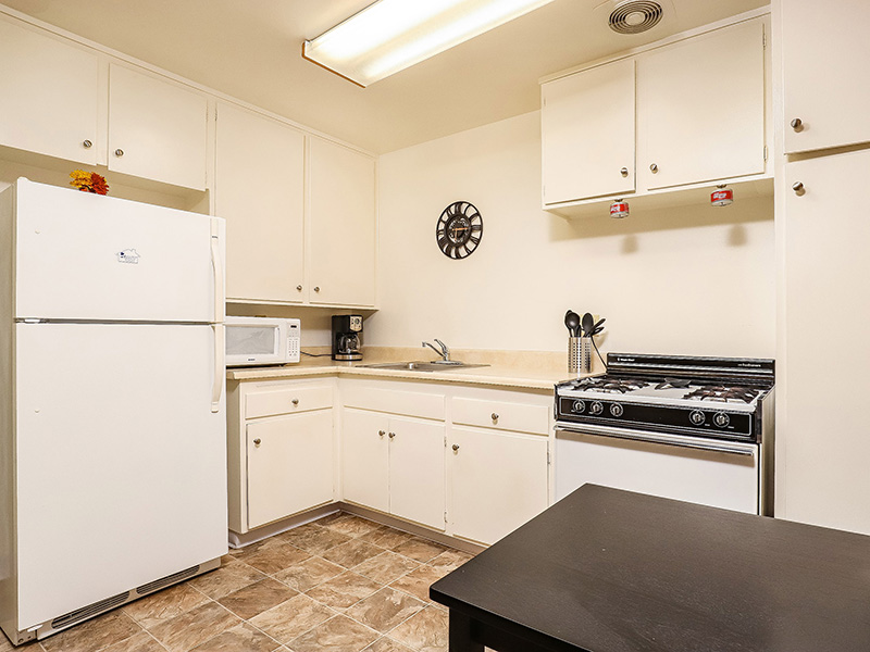 One bedroom kitchen with gas range, refrigerator and cabinets.