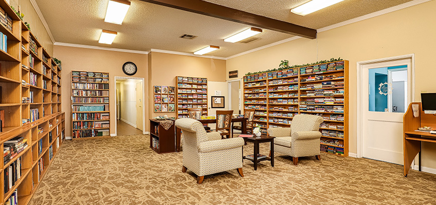 Library room with large shelves on several walls full of books.