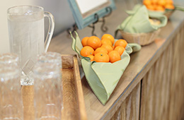glasses with a pitcher of water and oranges in a basket