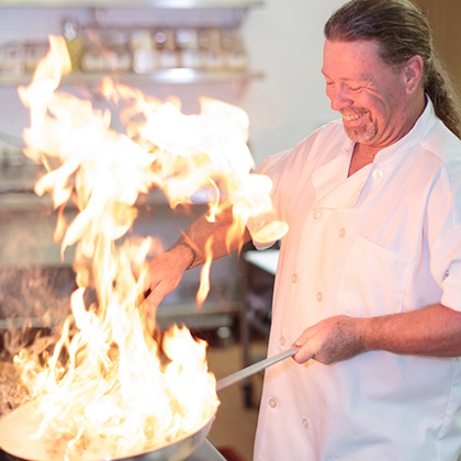 a chef smiling and cooking with a large fire
