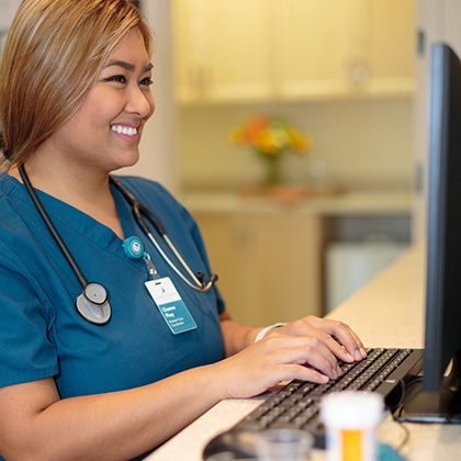 smiling nurse at a computer desk