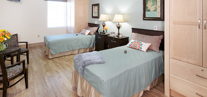 a two bed room with personal closets and tables