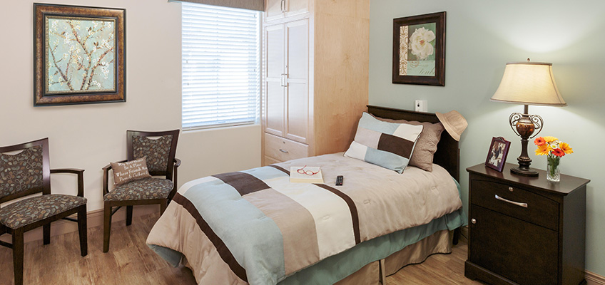 Beautifully decorated respite care room with a single bed, ample storage and comfortable seating