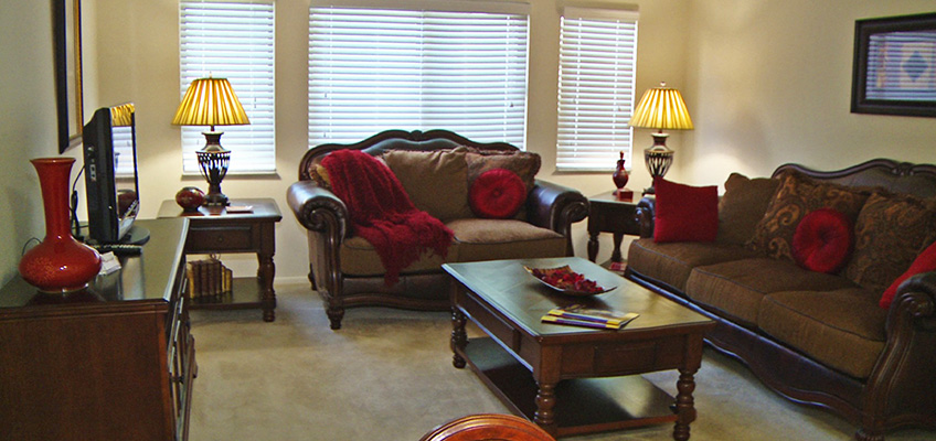 resident living room furnished with dark woods and leather couches with red accents