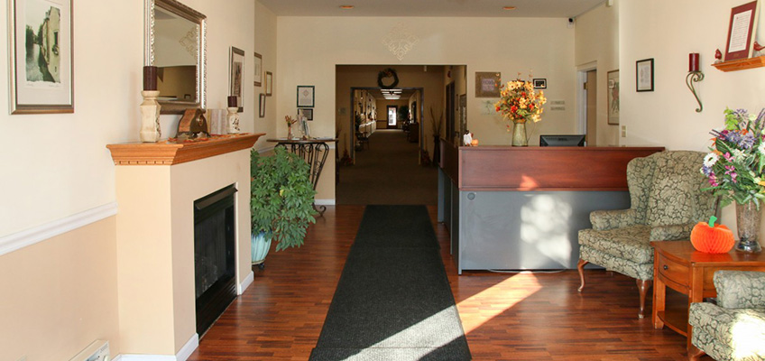 Lobby area with seating, wood floors colorful plants and a fireplace