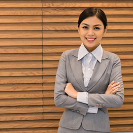 A woman in a business suite smiling with her arms folded in front of her