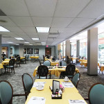 RHF Pioneer House dining room with colorful tablecloths and patterned carpet