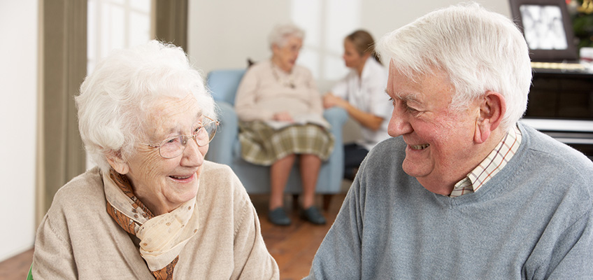 elderly couple smiling fondly at each other in the recreation room
